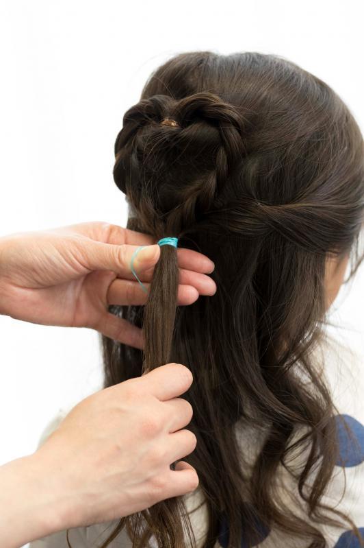 5.ハートを固定するために、両サイドの耳上の髪の毛とハートのしっぽをまとめてゴムで結ぶ。サイドの毛は、くるくるとねじりながらまとめると仕上がりがきれいになり